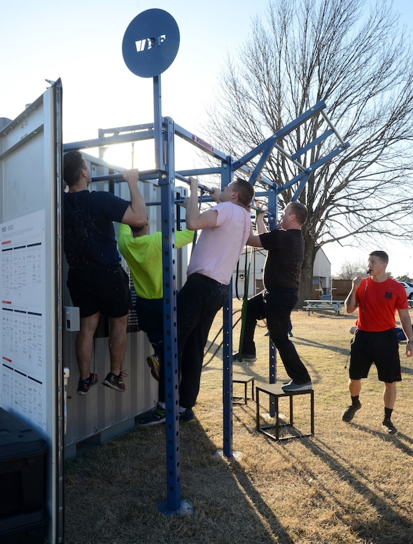 Tech. Sgt. Ricky Dent, right, an instructor at Airman Leadership School, oversees members of the current class as they perform pull-ups on the stations attached to the outside of the new Combat Cube.