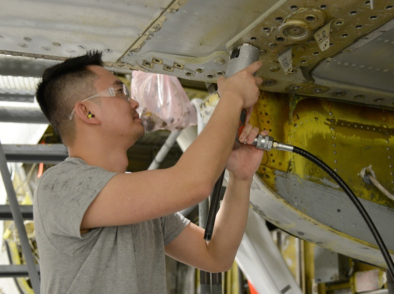 Jet Le, a sheetmetal mechanic with the 545th Aircraft Maintenance Squadron, pulls out a bolt on the boomerang section of the terminal of a KC-135 Stratotanker. Mr. Le has worked at Tinker for two years after completing the Pathway intern program through Francis Tuttle Technology Center.