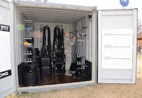 Tech. Sgt. Ricky Dent, an instructor at Tinker's Airman Leadership School, organizes the equipment inside the Combat Cube, which houses 2,000 pounds of weights, battle ropes, medicine balls and kettle bells, jump ropes, weight bars, stands, resistance bands and weighted sleds.