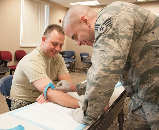 Tech. Sgt. Brett Haas of the 127th Maintenance Operation Flight receives a routine blood draw from Senior Airman Rick Burnett an aerospace medical technician with the 127th Medical Group on February 3,2018. Military members are required to fulfill mandated medical requirements annually to ensure readiness to deploy worldwide.