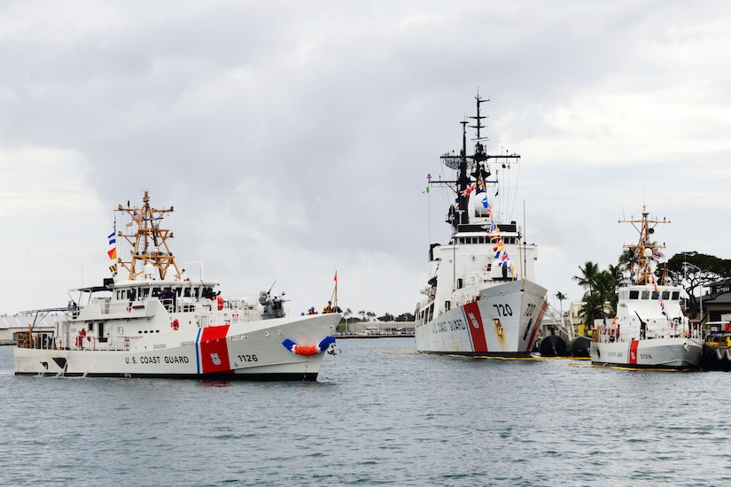 Three Coast Guard ships float together at a dock in Honolulu.