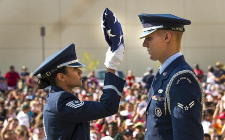 Members of the Travis Honor Guard present the flag in a ceremony held at Travis Air Force Base, Calif., Sept. 11, 2015 honoring the victims of the attacks on Sept. 11, 2001. The ceremony marked the beginning of the 2015 Freedom Walk. (U.S. Air Force photo by T.C. Perkins, Jr./Released)