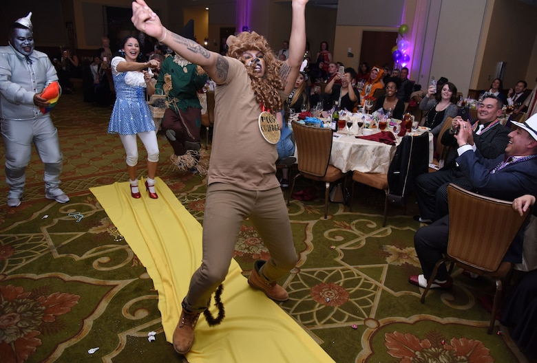 Senior Airman Rashawn Thompson, 81st Medical Operations Squadron mental health technician, dressed as the Cowardly Lion from The Wizard of Oz, dances down the aisle during a Mardi Gras float contest at the 30th Annual Krewe of Medics Mardi Gras Ball at the Bay Breeze Event Center Feb. 3, 2018, on Keesler Air Force Base, Mississippi. The Krewe of Medics hosts a yearly ball to give Keesler Medical Center personnel a taste of the Gulf Coast and an opportunity to experience a traditional Mardi Gras. The theme for this year's ball was Read It-Be It. The 81st MDOS won first place in the float contest. (U.S. Air Force photo by Kemberly Groue)