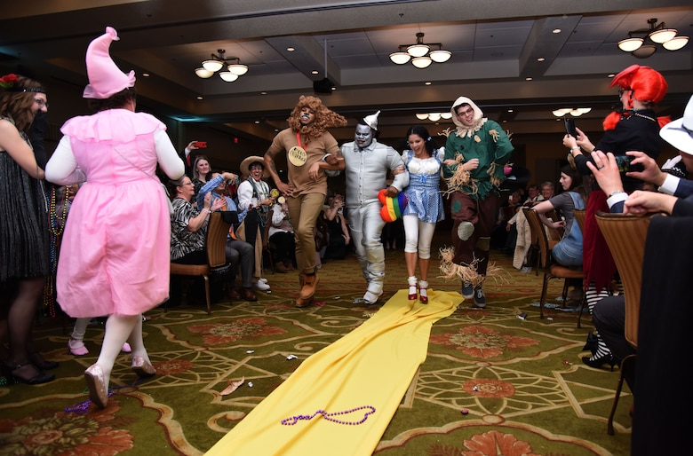 Members of the 81st Medical Operations Squadron portray the cast of The Wizard of Oz as they dance down the aisle during a Mardi Gras float contest at the 30th Annual Krewe of Medics Mardi Gras Ball at the Bay Breeze Event Center Feb. 3, 2018, on Keesler Air Force Base, Mississippi. The Krewe of Medics hosts a yearly ball to give Keesler Medical Center personnel a taste of the Gulf Coast and an opportunity to experience a traditional Mardi Gras. The theme for this year's ball was Read It-Be It. The 81st MDOS won first place in the float contest. (U.S. Air Force photo by Kemberly Groue)