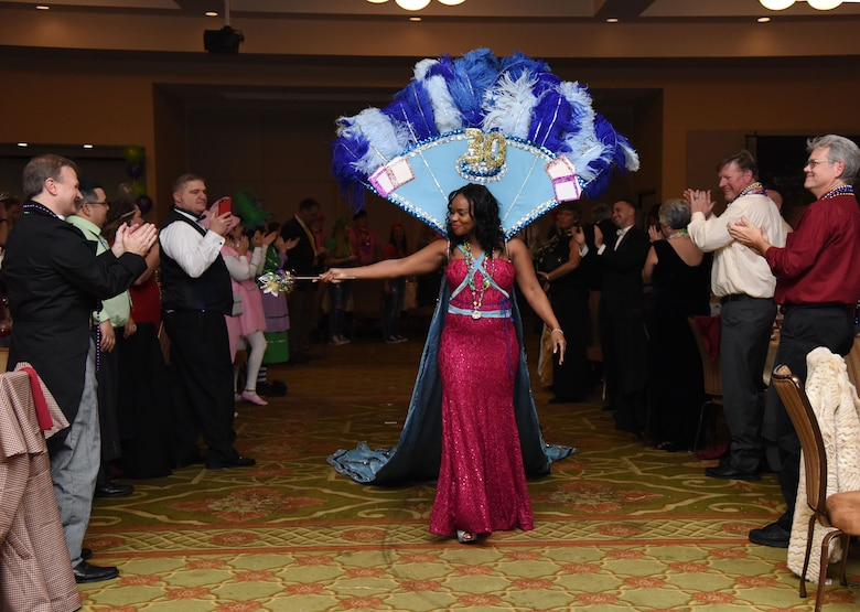 Capt. Melodee Jackson, 81st Surgical Operations Squadron, waves to the crowd after being named the 2018 Krewe of Medics queen during the 30th Annual Krewe of Medics Mardi Gras Ball at the Bay Breeze Event Center Feb. 3, 2018, on Keesler Air Force Base, Mississippi. The Krewe of Medics hosts a yearly ball to give Keesler Medical Center personnel a taste of the Gulf Coast and an opportunity to experience a traditional Mardi Gras. The theme for this year's ball was Read It-Be It. (U.S. Air Force photo by Kemberly Groue)