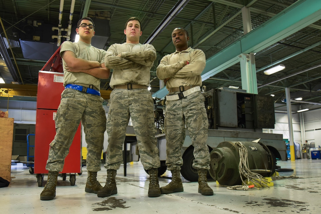 (From left) Airman 1st Class Christopher Palomares, Senior Airman Dustin Holmes, and Staff Sgt. Robert Gordon, 5th Maintenance Squadron aerospace ground equipment technicians, stand near a removed generator at Minot Air Force Base, N.D., Jan. 24, 2018. Aerospace ground equipment technicians are responsible for delivery, maintenance and inspection of equipment used on the flight line. (U.S. Air Force photo by Senior Airman Jessica Weissman)