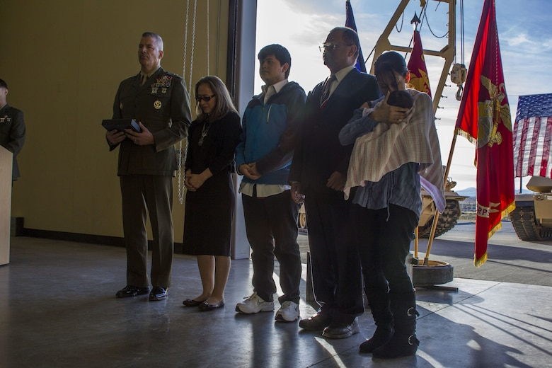 Major General William F. Mullen III, Commanding General, Marine Air Ground Task Force Training Command, Marine Corps Air Ground Combat Center, participates in an award ceremony with the family of Staff Sgt. Enrico Antonio Rojo at a memorial for Staff Sgt. Rojo aboard the Marine Corps Air Ground Combat Center, Twentynine Palms, Calif., Jan. 21, 2018. Staff Sgt. Rojo was awarded a Navy and Marine Corps Medal for attempting to help the victim of a car accident on December 16, 2016.(U.S. Marine Corps photo by Pfc. Rachel K. Porter)