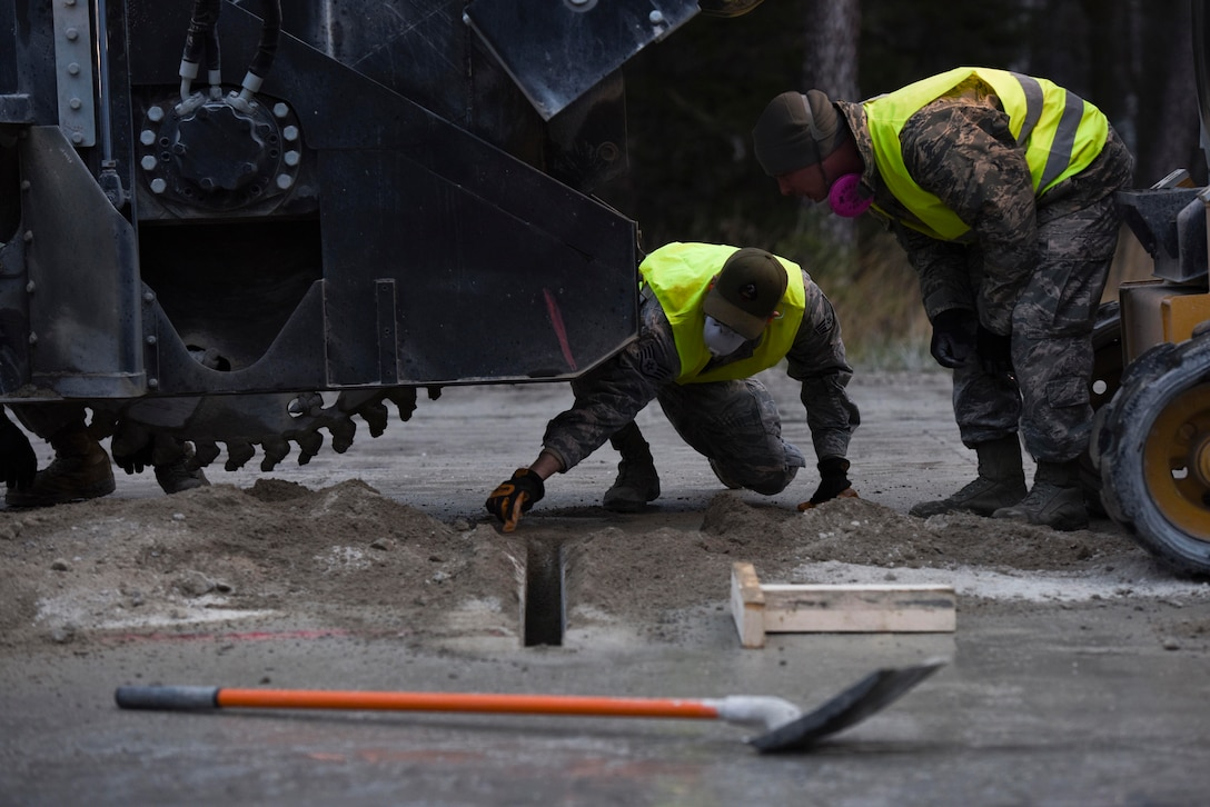 A U.S. Airman with the 435th Construction and Training Squadron training flight, and an Airman assigned to the 773rd Civil Engineer Squadron, checks the cuts made by the pavement team, during a Rapid Airfield Damage Repair training exercise on Ramstein Air Base, Germany, Jan. 25, 2018. The pavement teams were responsible for cutting the 18-24 inch deep concrete runway for other teams to clean out and repair. (U.S. Air Force photo by Senior Airman Devin M. Rumbaugh)