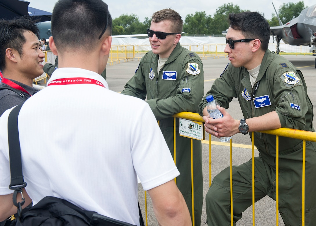 (Right) U.S. Air Force Capt. Christopher Richardson and Capt. Jonathan Keranen, 525th Fighter Squadron F-22 Raptor pilots, answer questions about their aircraft during the 2018 Singapore International Airshow at the Changi Exhibition Centre, Singapore, Feb. 6, 2018.