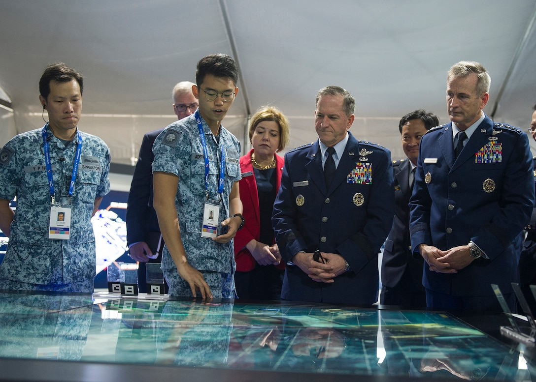 Gen. David L. Goldfein, U.S. Air Force chief of staff, Gen. Terrence J. O'Shaughnessy, Pacific Air Forces commander, and Heidi H. Grant, Deputy Under Secretary of the Air Force, International Affairs, receive a demonstration of a display during the 2018 Singapore International Airshow, Changi Exhibition Centre, Singapore, Feb. 6, 2018.