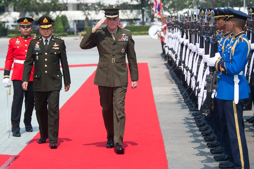 U.S, and Thai military leaders walk by an honor guard in Bangkok.