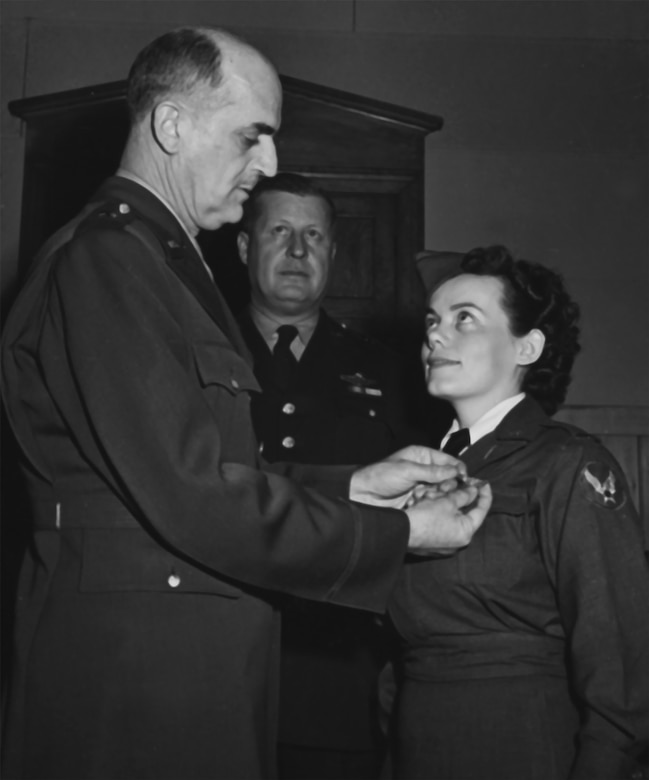 Brig. Gen. David N.W. Grant, Air Surgeon of the Army Air Forces, pins the wings on the blouse of 2nd Lt. Geraldine F. Dishroon, honor graduate of the flight nurse's school at Bowman Field, Kentucky, during the school's first formal flight nurse graduation on Feb. 18, 1943.  Brig. Gen. Fred S. Borum, Commanding General, 1st Troop Carrier Command, is in the center. (Photo courtesy of the National Archives)