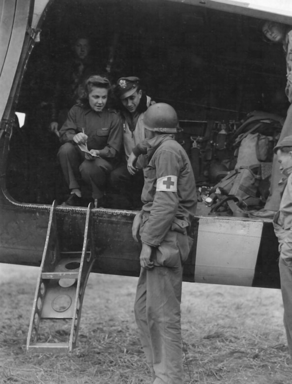 A Medical Corps Soldier gets last-minute instructions from the pilot and flight nurse before loading casualties aboard a Douglas C-47 air evacuation plane in France. (Photo courtesy of Air Force Medical Service Historian)