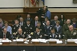 Military officials sit behind a desk with other civilians and military sitting behind them.