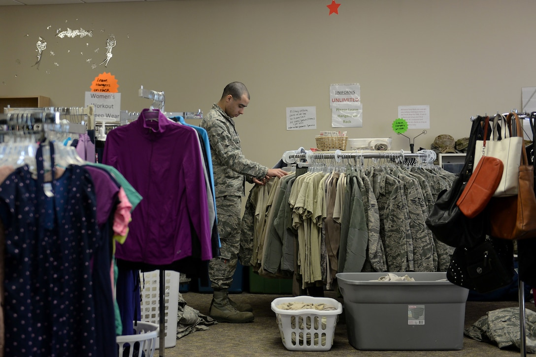 An Airman wearing the Air Force Battle Uniform grabs sand t-shirts while being surrounded by civilian clothes, purses and other military uniforms.