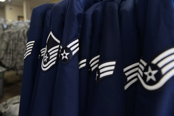 Air Force service jackets hung in a line with many different rank insignias including staff sergeant, senior airman, airman 1st class, master sergeant and technical sergeant.