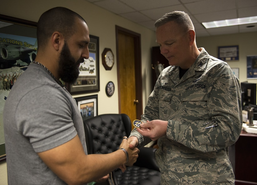 Mitchell Malloy, Gold Star family member, receives a 56th Fighter Wing coin from Col. Robert Sylvester, 56th Mission Support Group commander, at Luke Air Force Base, Ariz., Feb. 2, 2018. Malloy received a Defense Biometric Identification System Card that allows him access to all military installations. (U.S. Air Force Photo/Airman 1st Class Alexander Cook)