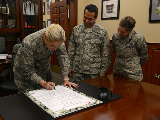 U.S. Air Force Col. April Vogel, commander of the 6th Air Mobility Wing, signs a proclamation for military saves week at MacDill Air Force Base, Fla., Feb. 1, 2018.