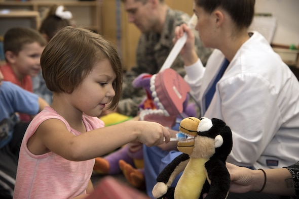 A child from the Child Development Center practices brushing teeth on a stuffed animal during a National Children's Dental Health Month presentation at MacDill Air Force Base, Fla., Feb. 6, 2018. Dental professionals, healthcare providers, and educators from MacDill take this opportunity to promote the benefits and importance of good oral health to children, their caregivers, teachers and many others. (U.S. Air Force photo by Airman 1st Class Ashley Perdue)