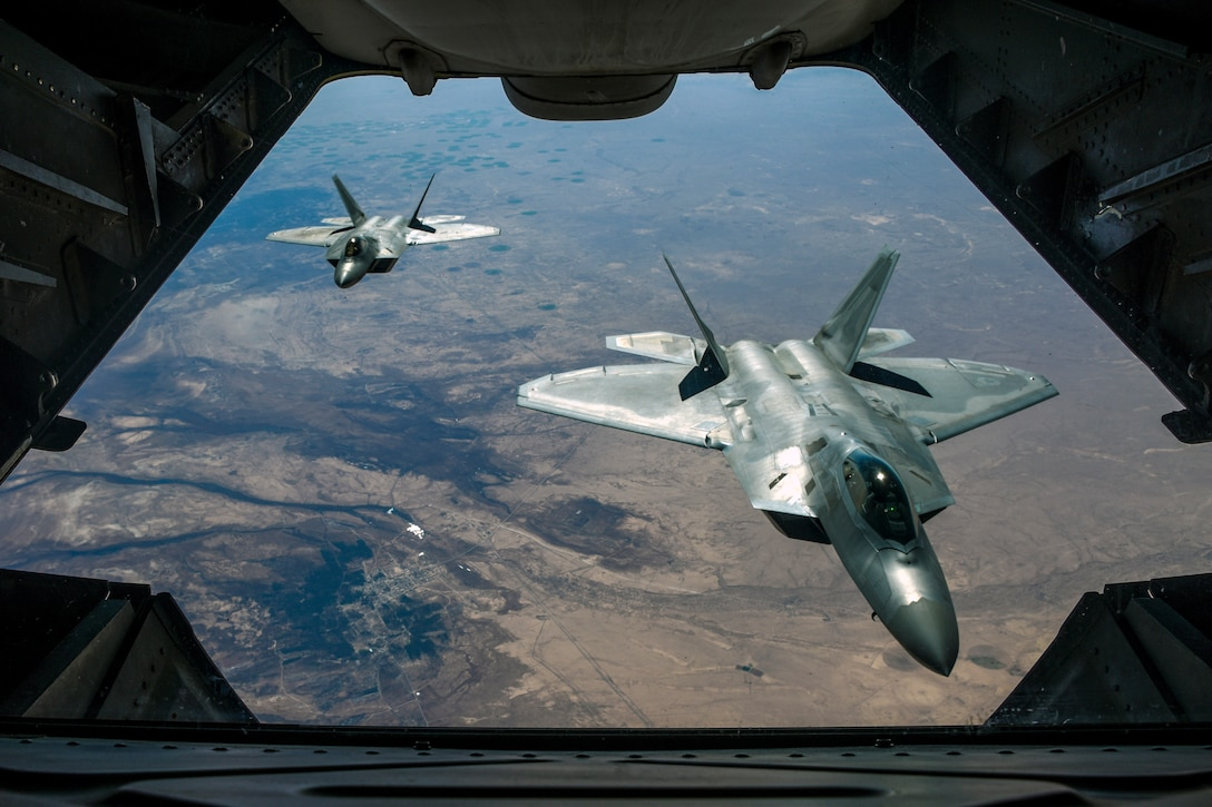 Two fighter jets, viewed from an opening in a third aircraft in front of them, fly over brownish terrain.