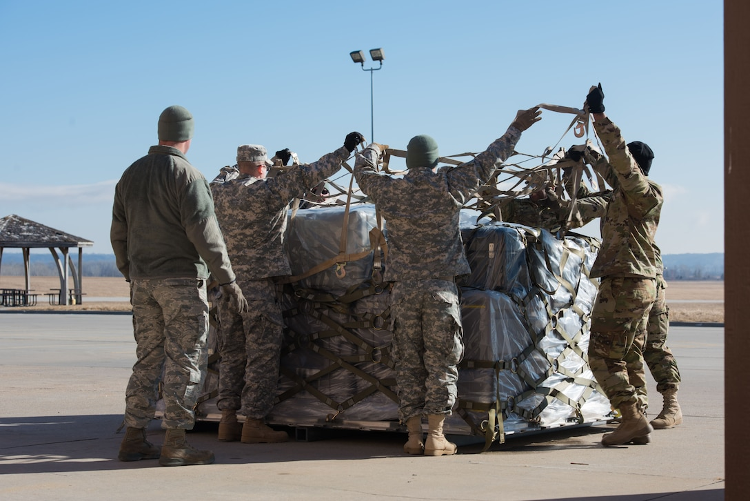 Soldiers from the U.S. Army Reserve 561st Regional Support Group, spread netting over a baggage pallet during a cargo preparation course at Offutt Air Force Base, Nebraska, Jan. 29, 2018. The Soldiers gained knowledge and skill in palletization, rolling stock, weighing, ways to protect and secure stock and the hazards to be aware of while working with air cargo. (U.S. Air Force photo by Senior Airman Jacob Skovo)