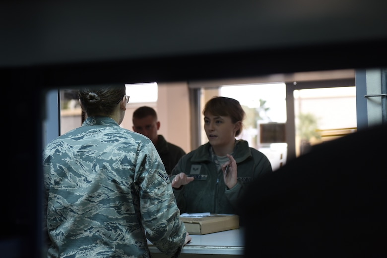 U.S. Air Force Airman Jodi Merritt, 39th Communications Squadron postal clerk, assists a customer receiving a package at Incirlik Air Base, Turkey, Jan. 16, 2018.