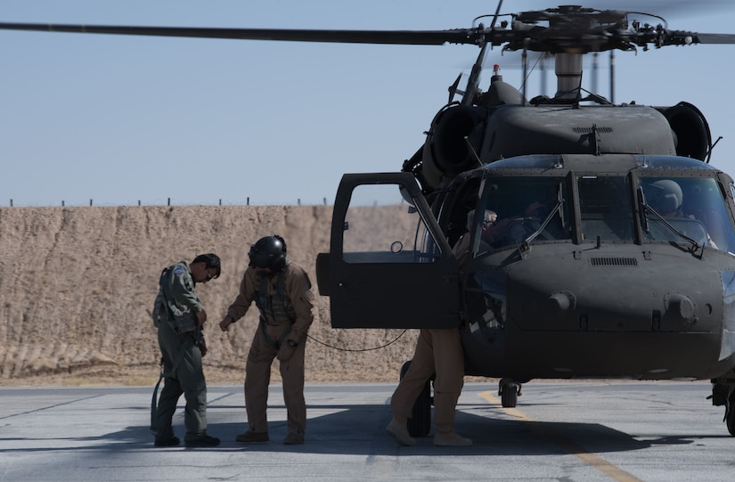 U.S. instructor pilots assist an Afghan Mi-17 pilot into a safety harness before his first orientation flight in the Afghan UH-60A Black Hawk Oct. 3, 2017, at Kandahar Airfield, Afghanistan. Mi-17 pilots are retraining to the Black Hawk and are expected to fly the aircraft by the end of 2017. The UH-60 is part of a multi-year modernization plan for the Afghan Air Force. (U.S. Air Force photo by Staff Sgt. Alexander W. Riedel)