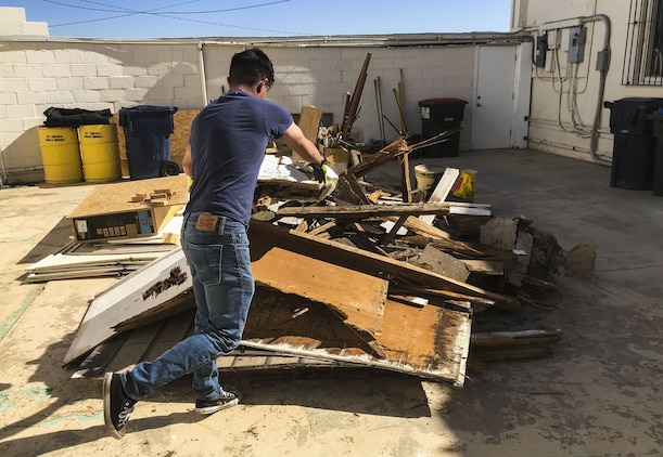U.S. Marine Corps Lance Cpl. Joel Soriano, a strategic communication specialist assigned to Marine Corps Air Station (MCAS) Yuma's Headquarters & Headquarters Squadron, moves rubble from a torn-down shed at St. Thomas Yuma Indian Mission in Winterhaven, Calif., Feb. 3, 2018. The mission, located out in the local Yuma community, requested help in tearing down the shed so that renovations could be made to the building. (U.S. Marine Corps photo taken by Cpl. Isaac Martinez)