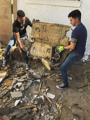 U.S. Marine Corps Cpl. Isaac D. Martinez and Lance Cpl. Joel Soriano, both strategic communication specialists with to Marine Corps Air Station (MCAS) Yuma's Headquarters & Headquarters Squadron, move a large piece of rubble from a torn-down shed at St. Thomas Yuma Indian Mission in Winterhaven, Calif., Feb. 3, 2018. The mission, located out in the local Yuma community, requested help in tearing down the shed so that renovations could be made to the building. (U.S. Marine Corps photo taken by Cpl. Isaac Martinez)
