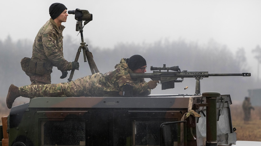 Army Spc. Joseph Swafford, top, spots for targets while Pvt. Jagger Onstott fires his Barrett .50-caliber rifle.