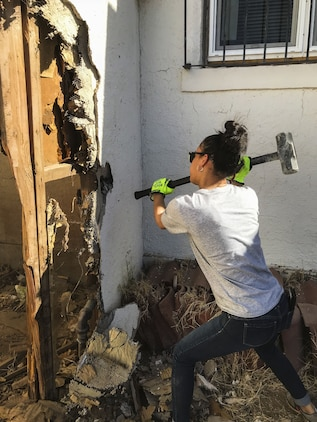 U.S. Marine Corps Lance Cpl. Adriana Adorno, a distribution management specialist assigned to Marine Corps Air Station (MCAS) Yuma's Headquarters & Headquarters Squadron, helps knock down part of a shed at St. Thomas Yuma Indian Mission in Winterhaven, Calif., Feb. 3, 2018. The mission, located out in the local Yuma community, requested help in tearing down the shed so that renovations could be made to the building. (U.S. Marine Corps photo taken by Cpl. Isaac Martinez)