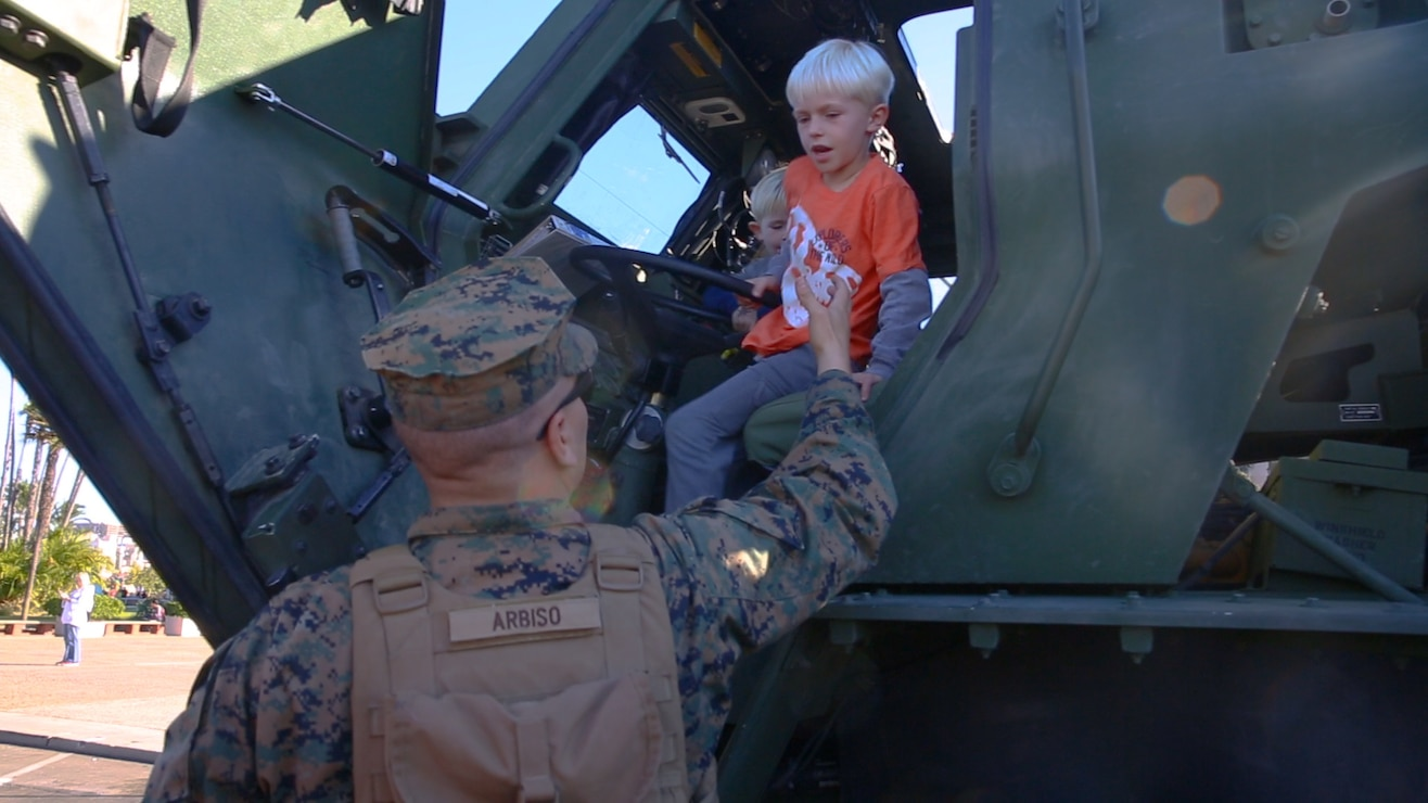 Pfc. Jacob Arbiscogautieri, a High Mobility Artillery Rocket System operator, with I Marine Expeditionary Force, helps children down from the cab of a HIMARS vehicle while it is staged prior to the San Diego County Credit Union Holiday Bowl Parade, Dec. 28, 2017. In 2017, I MEF Marines and Sailors supported more than 140 community events.