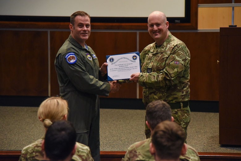U.S. Air Force Col. Sean C. Routier, F-35 Academic Training Center director, recognizes British Royal Air Force Sgt. Matthew Elwood, RAF Marham Aircrew Equipment Assemblies Maintenance Bay senior noncommissioned officer, as the 1000th international maintenance student Feb. 1, 2018, at Eglin Air Force Base, Fla. Since the ATC opened in 2011, it has graduated more than 5,500 maintainers and 361 pilots across three branches of service and ten participating countries. (U.S. Air Force photo by Airman 1st Class Emily Smallwood)