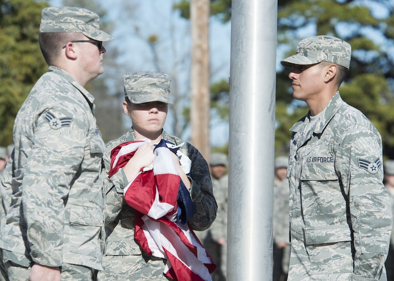 U.S. Air Force Senior Airmen Cody Burgan, left, Allison Burkett and Esteban Cruz, Senior Master Sgt. David B. Reid Airmen Leadership School flag detail team members, collect a flag at Shaw Air Force Base, S.C., Feb. 2, 2018.