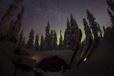 Participants of the Swedish Basic Winter Warfare Course sleep in the field under the sky covered with northern lights and stars in Arvidsjaur, Sweden, Jan. 23, 2018. Marines from the Black Sea Rotational Force and the 26th Marine Expeditionary Unit, along with troops from 9 other countries, participated in the Swedish Basic Winter Warfare Course. The course developed the participants' capability to survive in cold-weather environment, march on skis, apply his or hers tactical skills at individual and squad levels, and to lead smaller units in winter warfare in subarctic winter conditions. (U.S. Marine Corps photo by SSgt. Marcin Platek/Released)