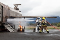 U.S. Marines with Aircraft Rescue Fire Fighting (ARFF) extinguish a wheel fire from a training aircraft during a wheel fire exercise at West Field, Marine Corps Air Station, Feb. 2, 2018. ARFF conducted a wheel fire exercise to improve proficiency in assessing and extinguishing a fire by utilizing the Mobile Aircraft Firefighting Training Device. (U.S. Marine Corps photo by Cpl. Jesus Sepulveda Torres)
