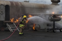 U.S. Marines with Aircraft Rescue Fire Fighting (ARFF) extinguish a fire from a training aircraft during a wheel fire exercise at West Field, Marine Corps Air Station, Feb. 2, 2018. ARFF conducted a wheel fire exercise to improve proficiency in assessing and extinguishing a fire by utilizing the Mobile Aircraft Firefighting Training Device. (U.S. Marine Corps photo by Cpl. Jesus Sepulveda Torres)