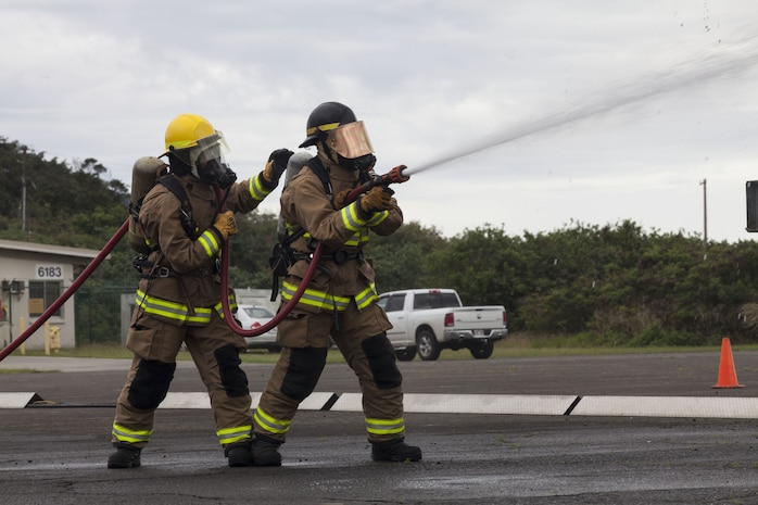U.S. Marines with Aircraft Rescue Fire Fighting (ARFF) use a water hose on a training aircraft engulfed in flames during a wheel fire exercise at West Field, Marine Corps Air Station, Feb. 2, 2018. ARFF conducted a wheel fire exercise to improve proficiency in assessing and extinguishing a fire by utilizing the Mobile Aircraft Firefighting Training Device. (U.S. Marine Corps photo by Cpl. Jesus Sepulveda Torres)