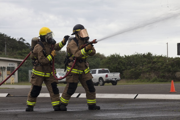 us marines with aircraft rescue fire fighting arff use a water hose on a