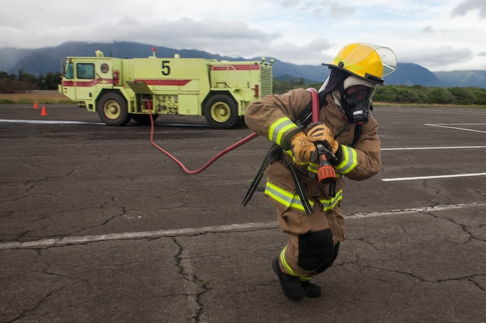 A U.S. Marine with Aircraft Rescue Fire Fighting (ARFF) unrolls a firehose from a P-19 Firefighting Vehicle during a wheel fire exercise at West Field, Marine Corps Air Station, Feb. 2, 2018. ARFF conducted a wheel fire exercise to improve proficiency in assessing and extinguishing a fire by utilizing the Mobile Aircraft Firefighting Training Device. (U.S. Marine Corps photo by Cpl. Jesus Sepulveda Torres)