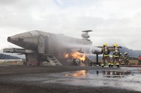 U.S. Marines with Aircraft Rescue Fire Fighting (ARFF), extinguish a live fire from a training aircraft during a wheel fire exercise at West Field, Marine Corps Air Station, Feb. 2, 2018. ARFF conducted a wheel fire exercise to improve proficiency in assessing and extinguishing a fire by utilizing the Mobile Aircraft Firefighting Training Device. (U.S. Marine Corps photo by Cpl. Jesus Sepulveda Torres)