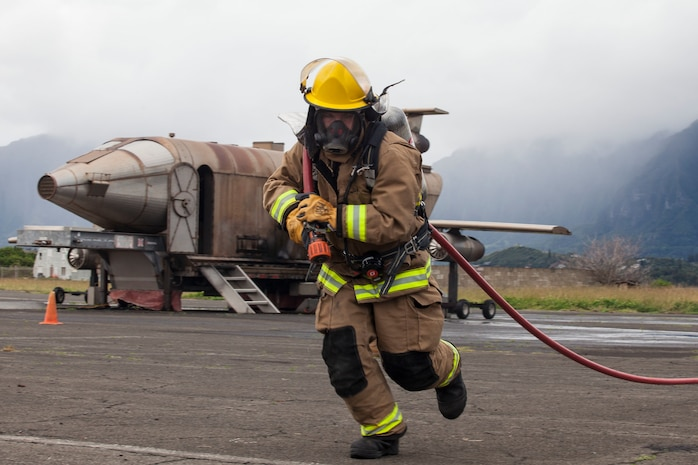 A U.S. Marine with Aircraft Rescue Fire Fighting (ARFF) unrolls a firehose during a wheel fire exercise at West Field, Marine Corps Air Station, Feb. 2, 2018. ARFF conducted a wheel fire exercise to improve proficiency in assessing and extinguishing a fire by utilizing the Mobile Aircraft Firefighting Training Device. (U.S. Marine Corps photo by Cpl. Jesus Sepulveda Torres)