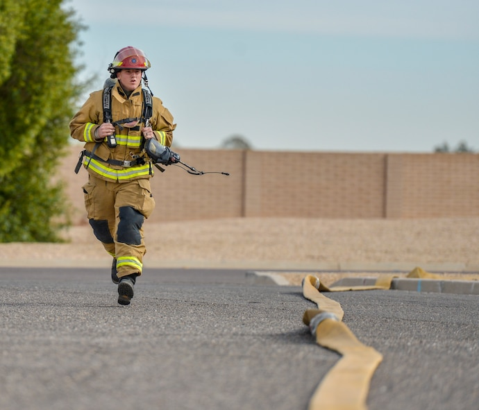 An Airman assigned to the 56th Civil Engineer Squadron runs to the scene of a simulated fire during structural firefighting training at Luke Air Force Base, Ariz., Jan. 16, 2018. Firefighters use hands-on, realistic training scenarios to better prepare them for real-world situations. (U.S. Air Force photo/Airman 1st Class Caleb Worpel)