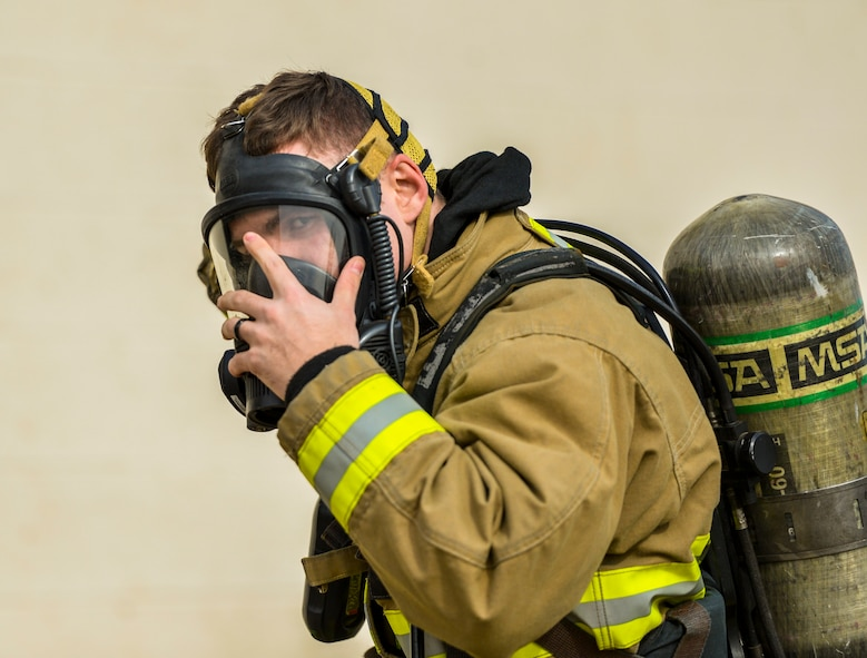 An Airman assigned to the 56th Civil Engineer Squadron puts on an oxygen respirator during structural firefighting training at Luke Air Force Base, Ariz., Jan. 16, 2018. Firefighters use hands-on, realistic training scenarios to better prepare them for real-world situations. (U.S. Air Force photo/Airman 1st Class Caleb Worpel)