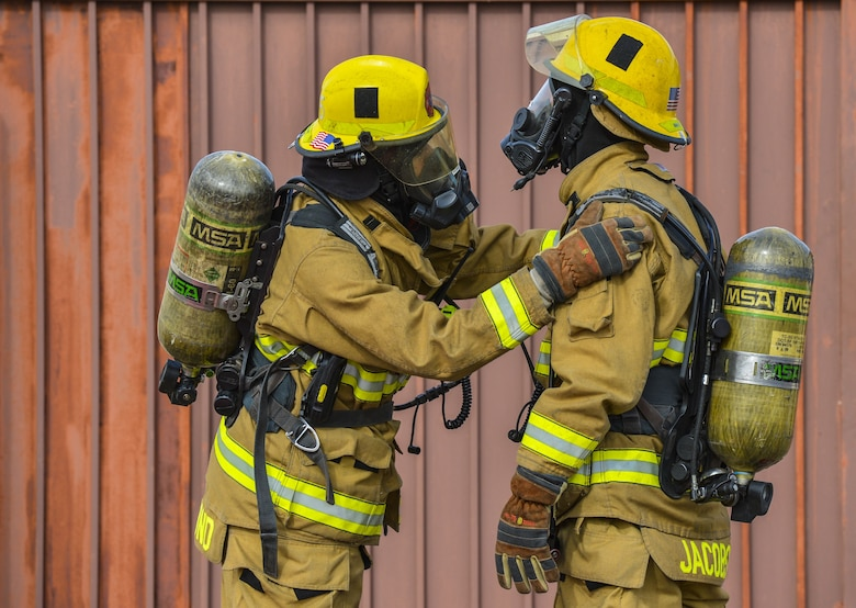 Airmen assigned to the 56th Civil Engineer Squadron check each other's gear in preparation for structural firefighting training at Luke Air Force Base, Ariz., Jan. 16, 2018. The goal of the training was to clear heat and smoke from a contained structure to increase chances of survival for occupants trapped inside. (U.S. Air Force photo/Airman 1st Class Caleb Worpel)