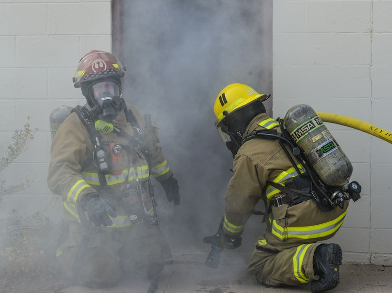 Airmen assigned to the 56th Civil Engineer Squadron prepare to enter a smoky building during structural firefighting training at Luke Air Force Base, Ariz., Jan. 16, 2018. The purpose of the training was to clear heat and smoke from a contained structure increasing chances of survival for trapped occupants. (U.S. Air Force photo/Airman 1st Class Caleb Worpel)