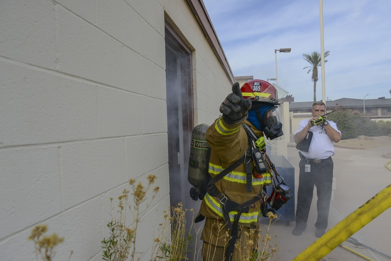 An Airman assigned to the 56th Civil Engineer Squadron gives directions to other firefighters during structural firefighting training at Luke Air Force Base, Ariz., Jan. 16, 2018. The goal of the training was to clear heat and smoke from a contained structure increasing chances of survival for trapped occupants. (U.S. Air Force photo/Airman 1st Class Caleb Worpel)