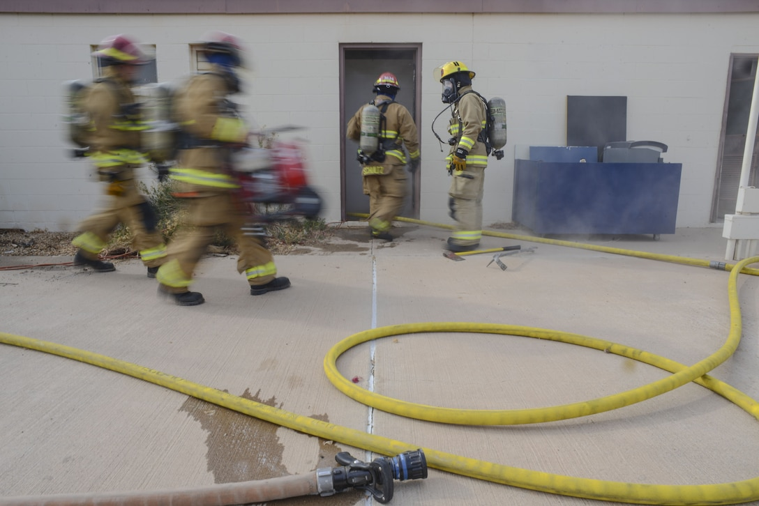 Airmen assigned to the 56th Civil Engineer Squadron enter a building during structural firefighting training at Luke Air Force Base, Ariz., Jan. 16, 2018. The goal of the training was to clear heat and smoke from a contained structure to increase chances of survival for occupants trapped inside. (U.S. Air Force photo/Airman 1st Class Caleb Worpel)
