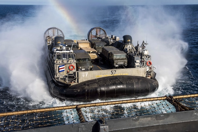 An air-cushioned landing craft approaches a ship as a rainbow forms over it.