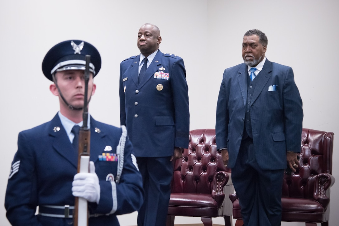 Maj. Gen. Mark Brown, Air Education and Training Command deputy commander, and Gary Wallace, 53rd Weather Reconnaissance Squadron aviation resource management technician, stand at attention while members of the Keesler Honor Guard present the colors for Wallace's retirement ceremony Feb. 2, 2018 at Keesler Air Force Base, Mississippi. (U.S. Air Force photo by Staff Sgt. Heather Heiney)